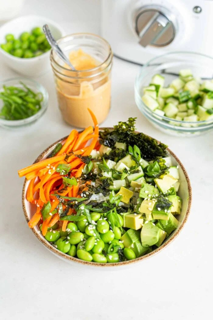 Rice, cucumber, seaweed, avocado, edamame and carrot in a bowl.