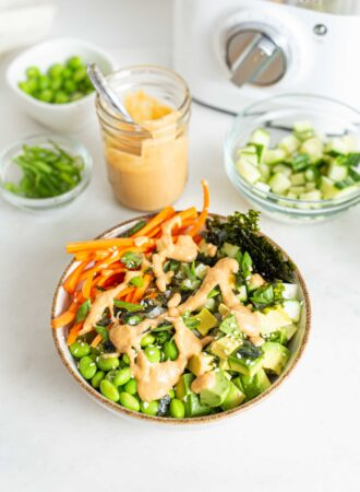 Carrot, edamame, rice, cucumber and nori topped with sauce in a bowl.