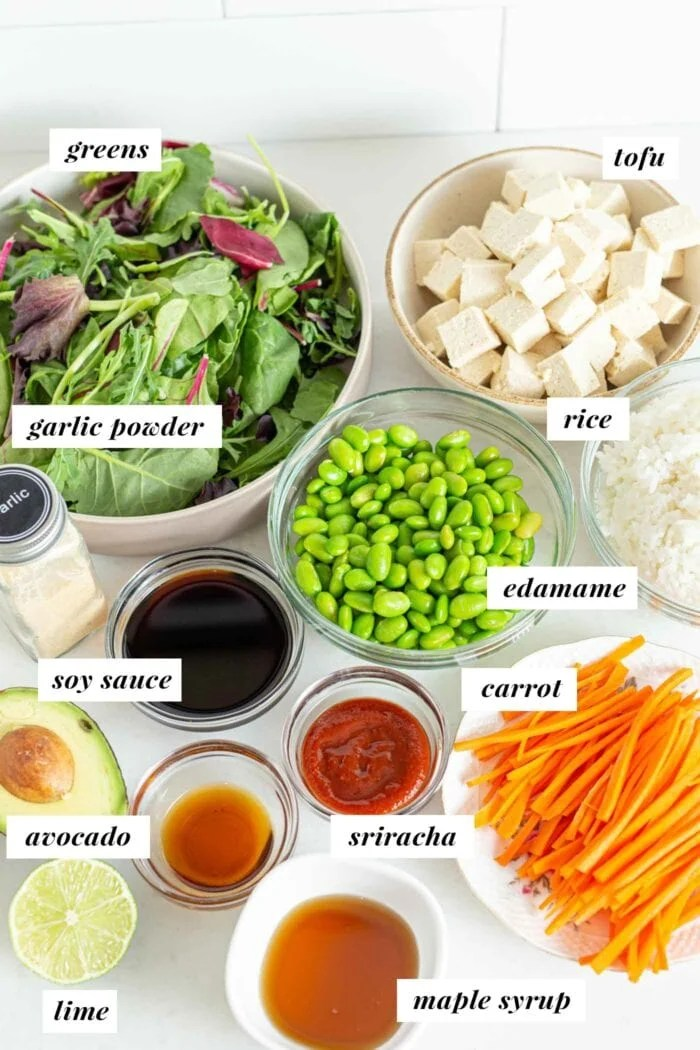 Sliced carrot, greens, sauces, edamame, rice and tofu in bowls.