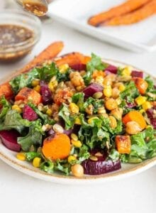 Bowl of kale salad with beet, corn, carrots and pumpkin seeds.