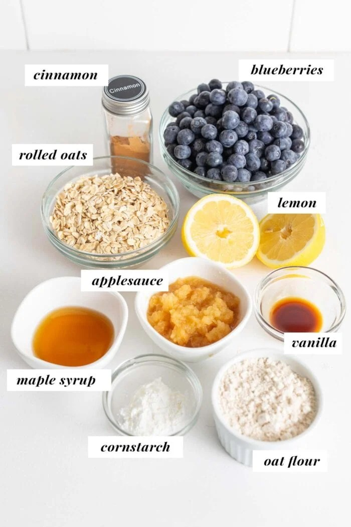 Blueberries, oats, oat flour, cinnamon, applesauce and maple syrup in dishes on a counter.