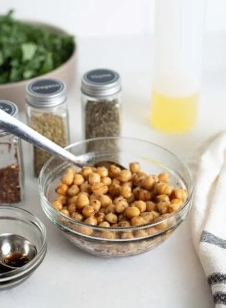Chickpeas with balsamic vinegar and herbs in a small bowl with a spoon,