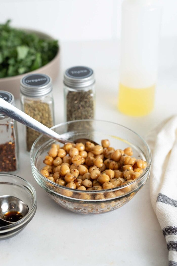 Marinated chickpeas in a bowl with a spoon.