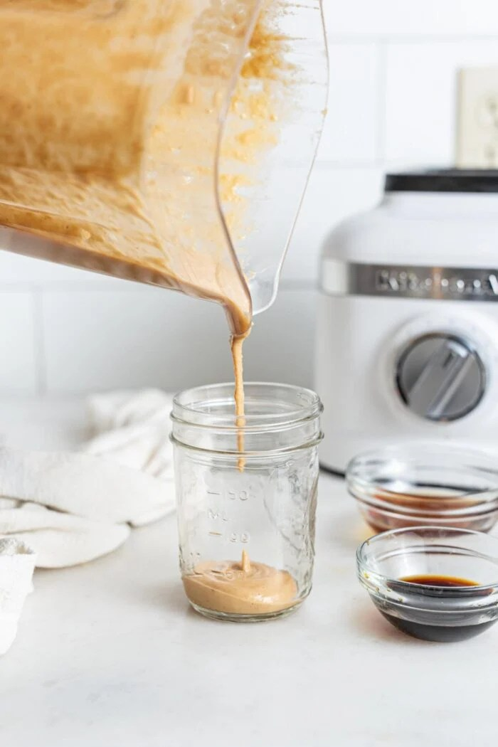 Pouring sauce from a blender into a glass jar.