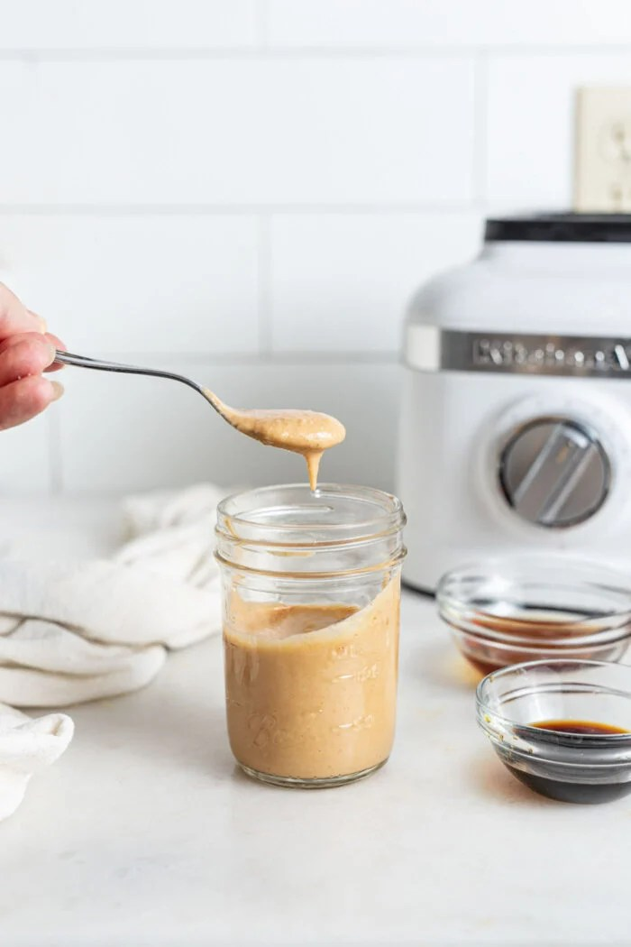 Scooping a spoonful of sauce out of a small jar.