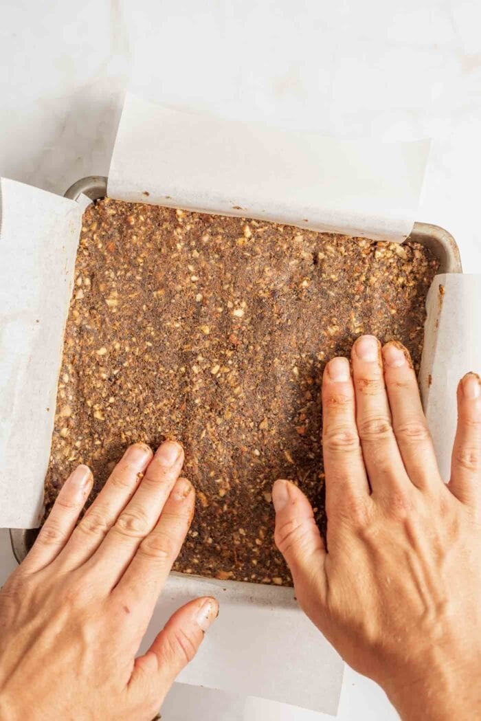 Two hands flattening energy bar dough in a a parchment paper-lined metal baking pan.