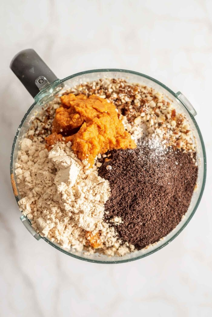 Pumpkin puree, ground coffee and protein powder sitting on top of a crumbly mixture in a food processor.