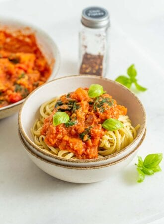 Bowl of pasta noodles with tomato vegetable sauce and fresh basil on top.