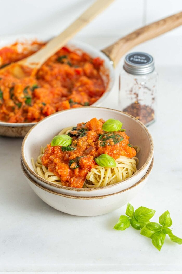 A bowl of tomato pasta with fresh basil, skillet of tomato sauce in the backgroun.
