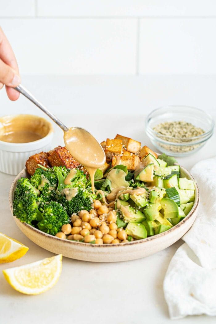 Adding a spoonful of tahini to a bowl of chickpea, broccoli, tofu, cucumber and tempeh salad.