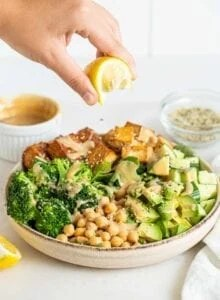 Squeezing lemon over a bowl of green salad with tofu, tempeh and chickpeas.