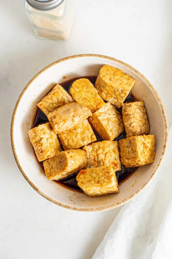 Cubed tempeh mixed in a small bowl with marinade.