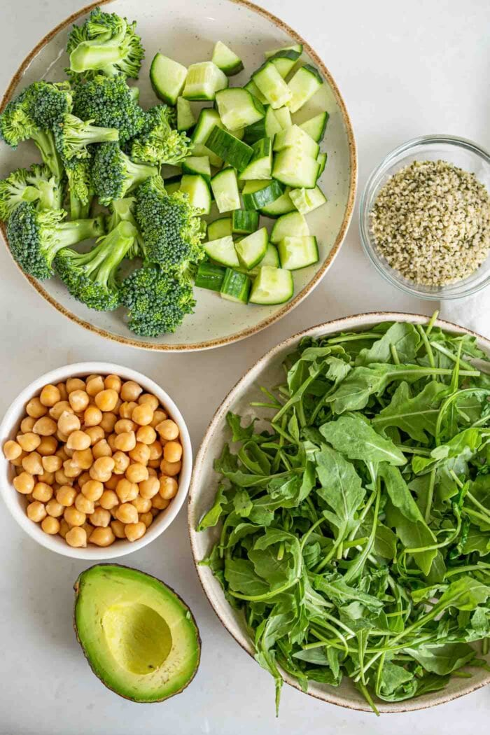 Chickpeas, hemp seeds, avocado, arugula and broccoli on a counter.