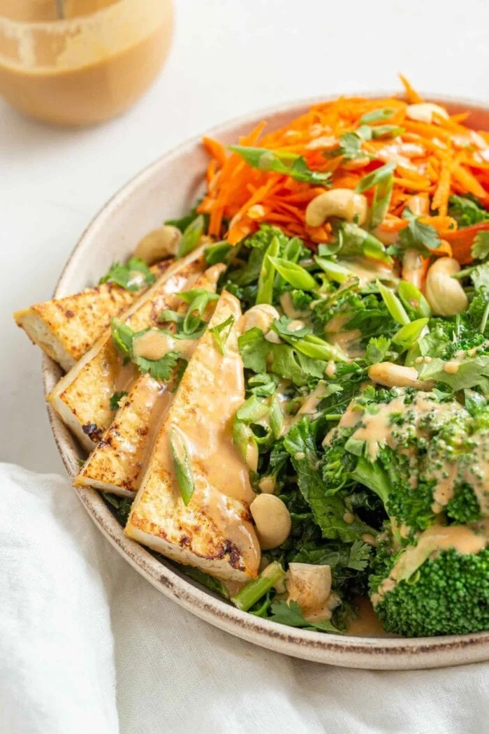 Large triangles of crispy tofu in a salad with kale and broccoli.