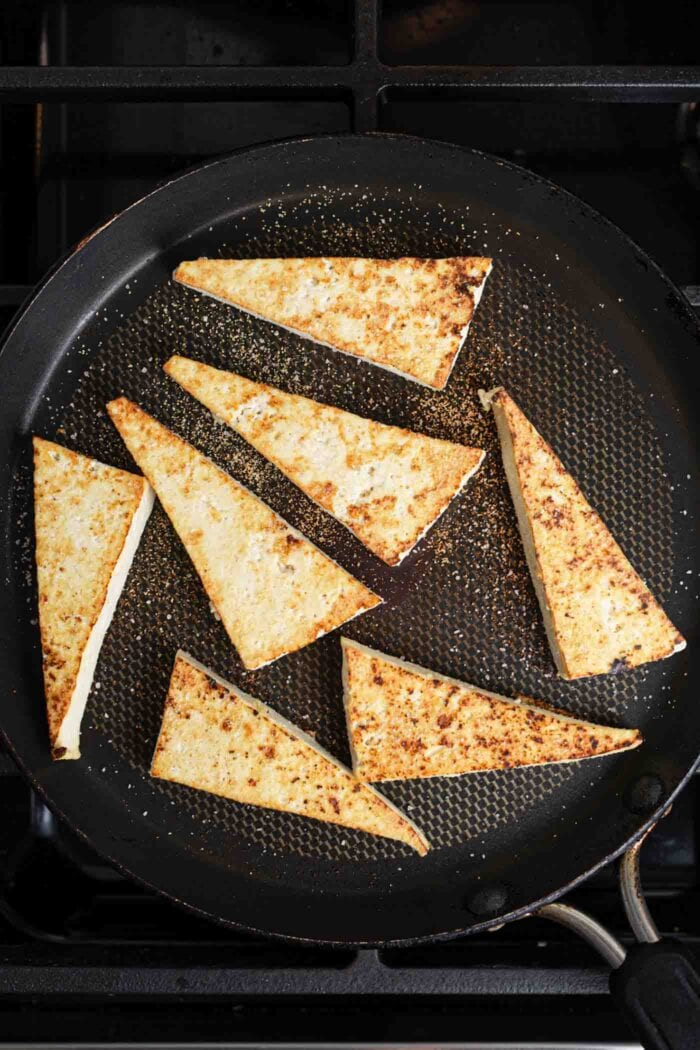 Triangles of tofu cooking in a skillet.