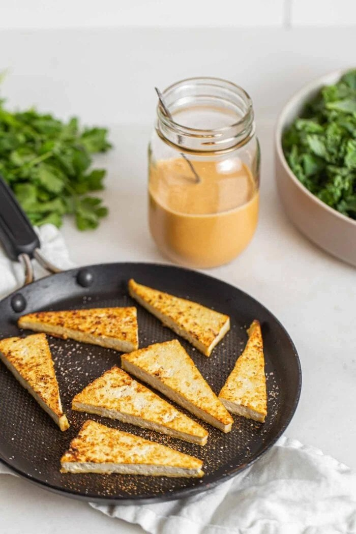 Browned tofu triangles in a skillet on a counter.