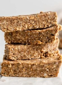 A stack of 4 energy bars with a few almonds scattered around them.