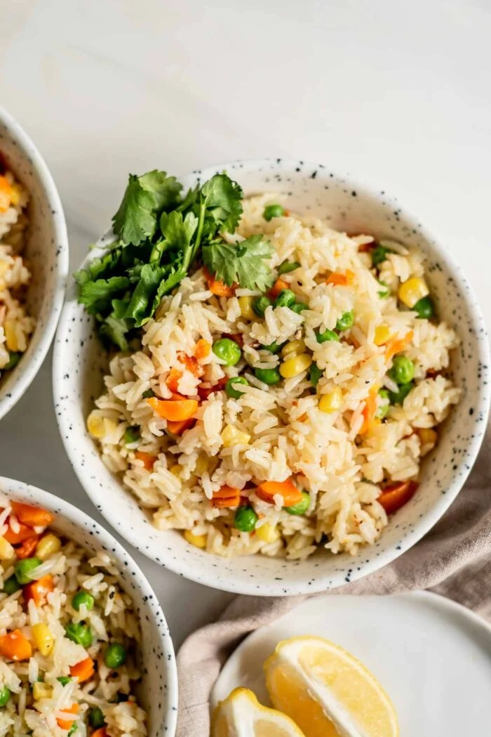 A bowl of rice pilaf with peas, corn and carrots and some cilantro on the side, two more bowls sitting just out of the frame.