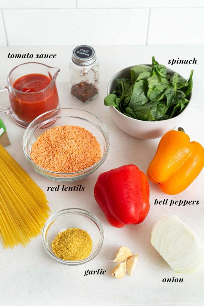 Labelled ingredients for making red lentil pasta sauce.