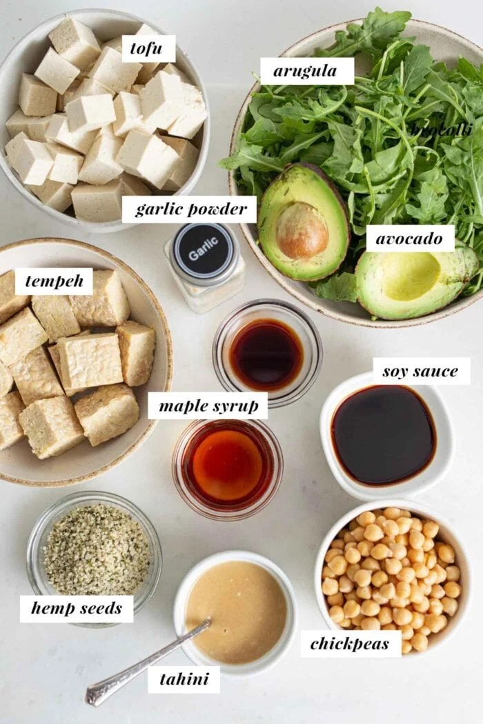 Labelled ingredients in bowls for making a vegan high-protein salad bowl.