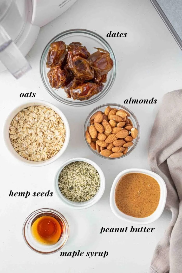 Dates, almonds, peanut butter, maple syrup and oats labelled in small dishes.