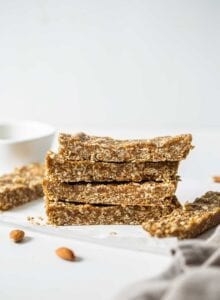 A stack of 4 energy bars on a counter with a few almonds scattered around them.