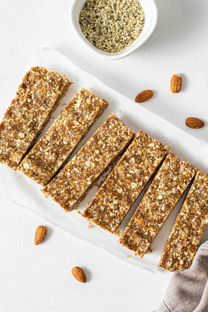 6 energy bars on top of parchment paper with a few almonds scattered around them.