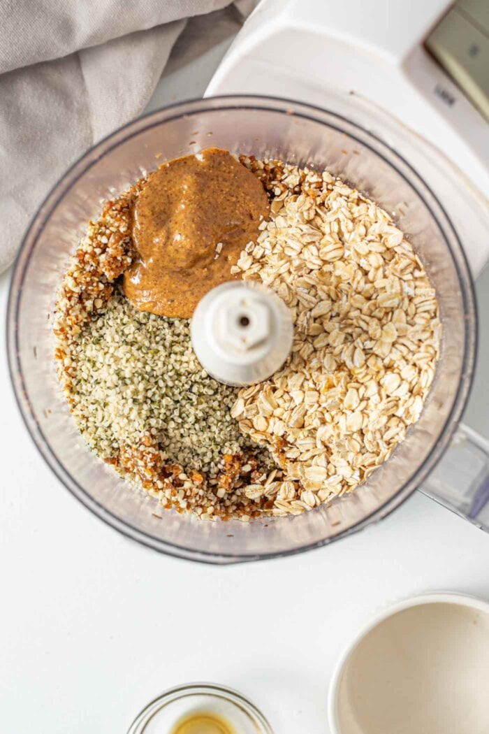 Oats, peanut butter and hemp seeds in a food processor.
