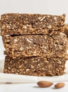 Stack of 3 energy bars on parchment paper with some almonds in the foreground.