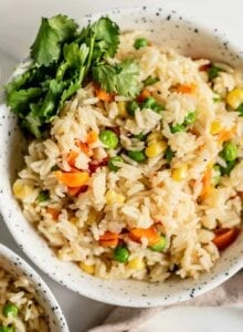 A bowl of rice pilaf with peas, corn and carrots and some cilantro on the side.