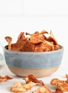Bowl of baked apple chips with cinnamon on them.