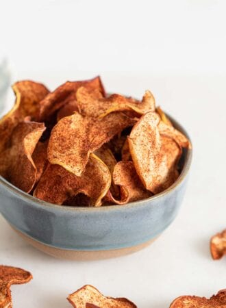 Bowl of baked apple chips, a few scattered around the bowl.