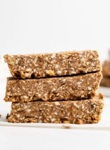 Stack of 3 energy bars sitting on a folded piece of parchment paper. More bars in background.