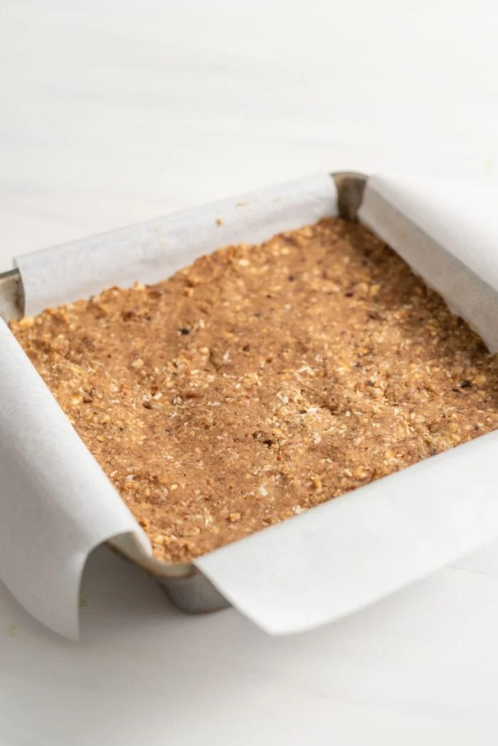 Parchment paper-lined square baking pan of energy bars.