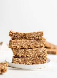 Stack of 4 energy bars on a small plate. More bars in foreground and background.