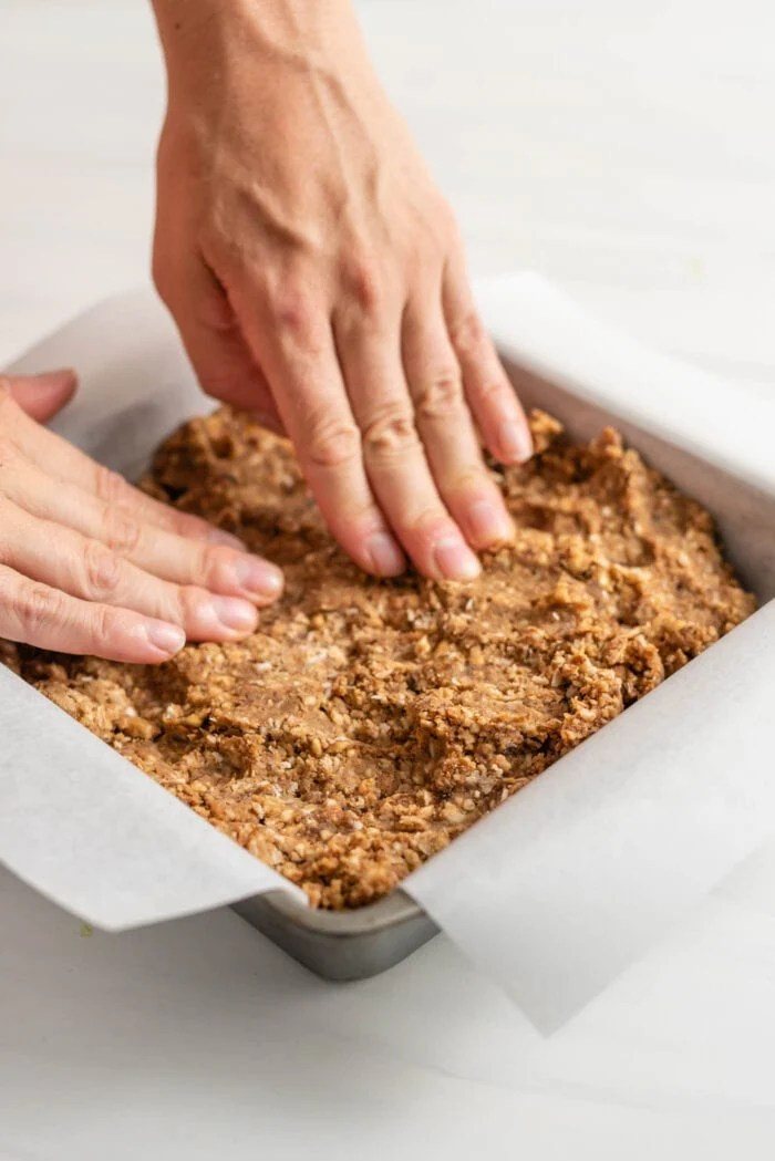 Two hands pressing dough into a square baking pan.