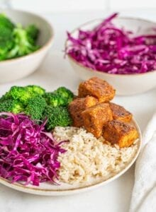 Bowl of brown rice, broccoli, sliced red cabbage and baked tempeh cubes.