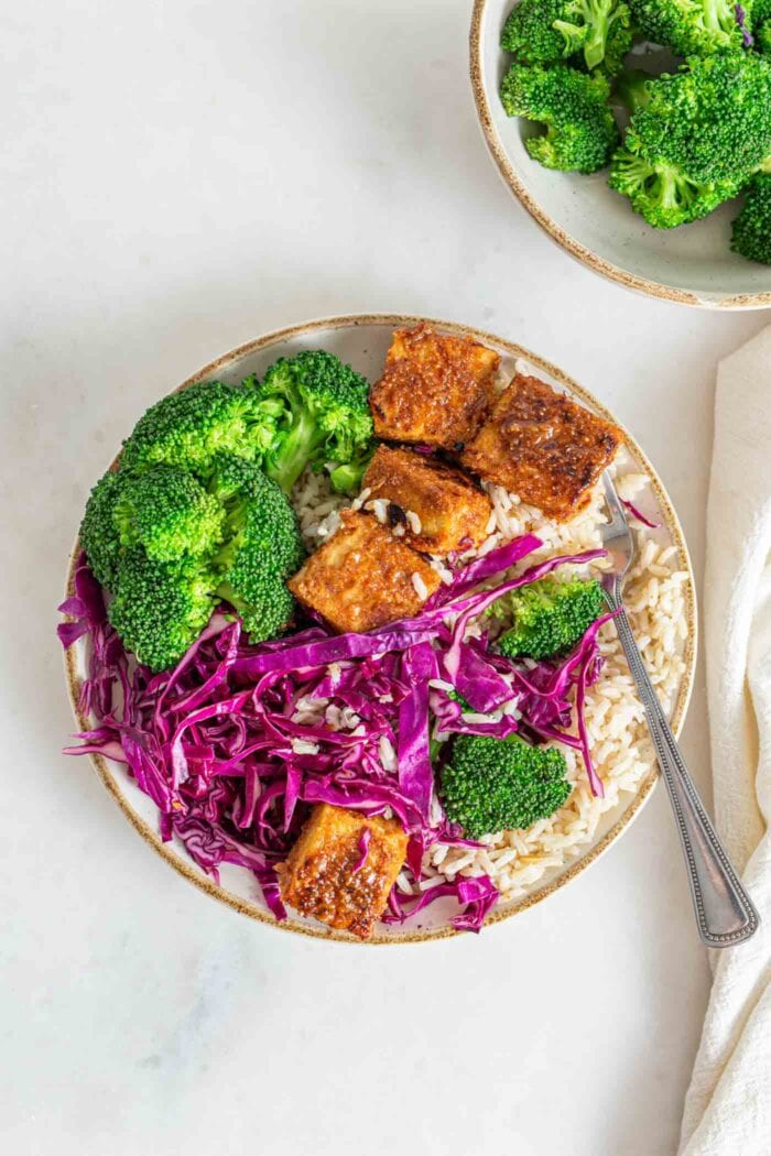 Buddha bowl with broccoli, brown rice, tempeh and thinly sliced red cabage.