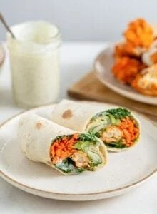 Two halves of a buffalo cauliflower wrap with avocado on a plate, inside of wraps is showing.