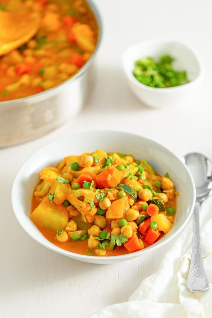 Bowl of stew with vegetables, chickpeas and peas. Pot of stew in background.