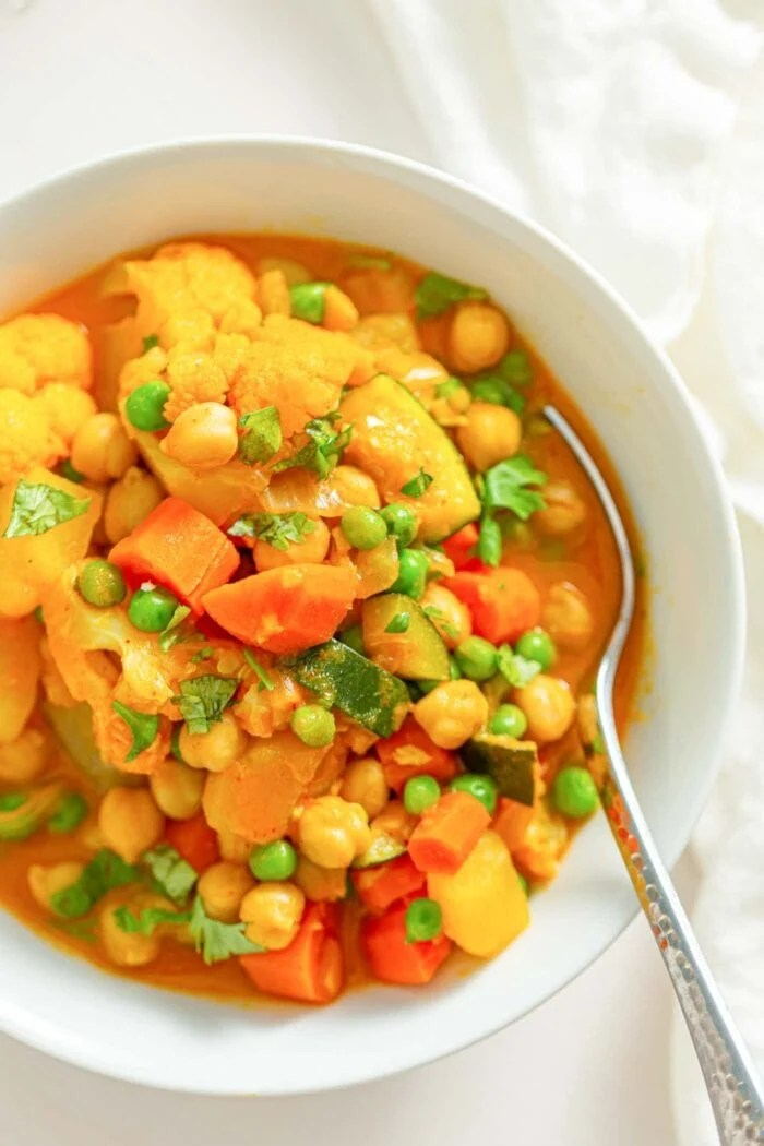 Overhead close up image of a bowl of stew with vegetables, chickpeas and peas.