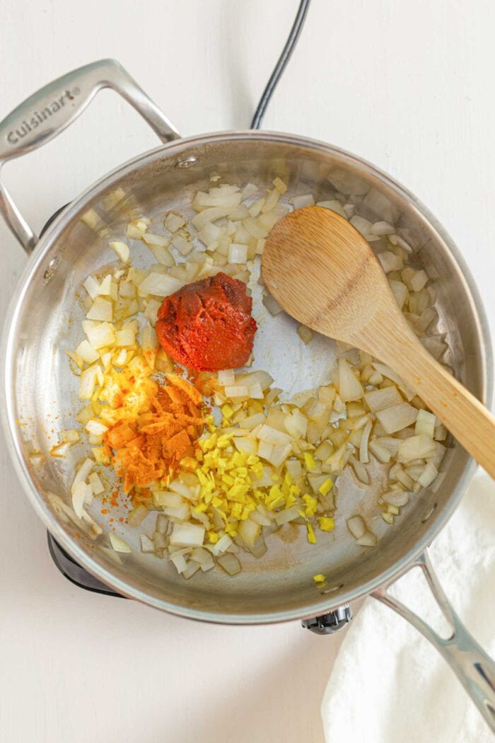 Onions, garlic, curry paste, ginger and turmeric cooking in a large pot.
