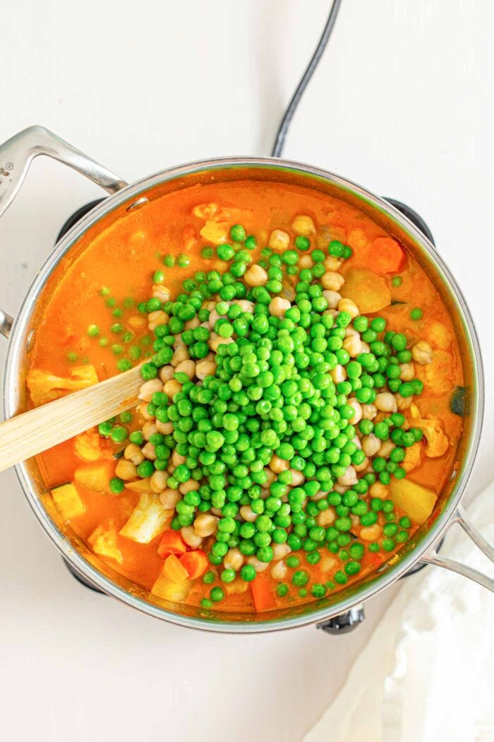 Adding peas and chickpeas to a large pot of stew. Wooden spoon rests in pot.