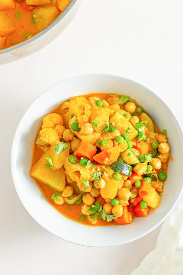 Overhead image of bowl of stew with potato, chickpeas, peas and carrots.
