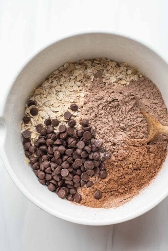 Protein powder, cocoa powder, chocolate chips and oats in a mixing bowl.