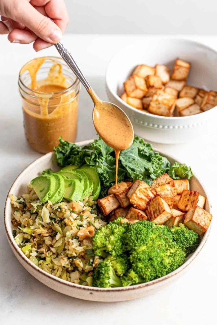 Drizzling a spoonful of sauce over a bowl with tofu, avocado and veggies.