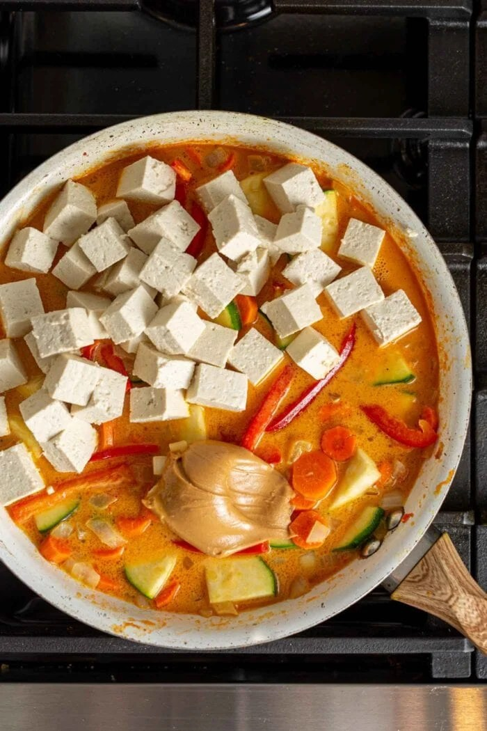 Tofu and peanut butter being added to a vegetable curry in a skillet.