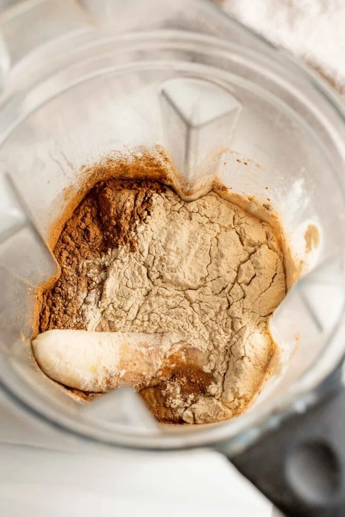 Milk, banana, cinnamon and protein powder in a blender container.