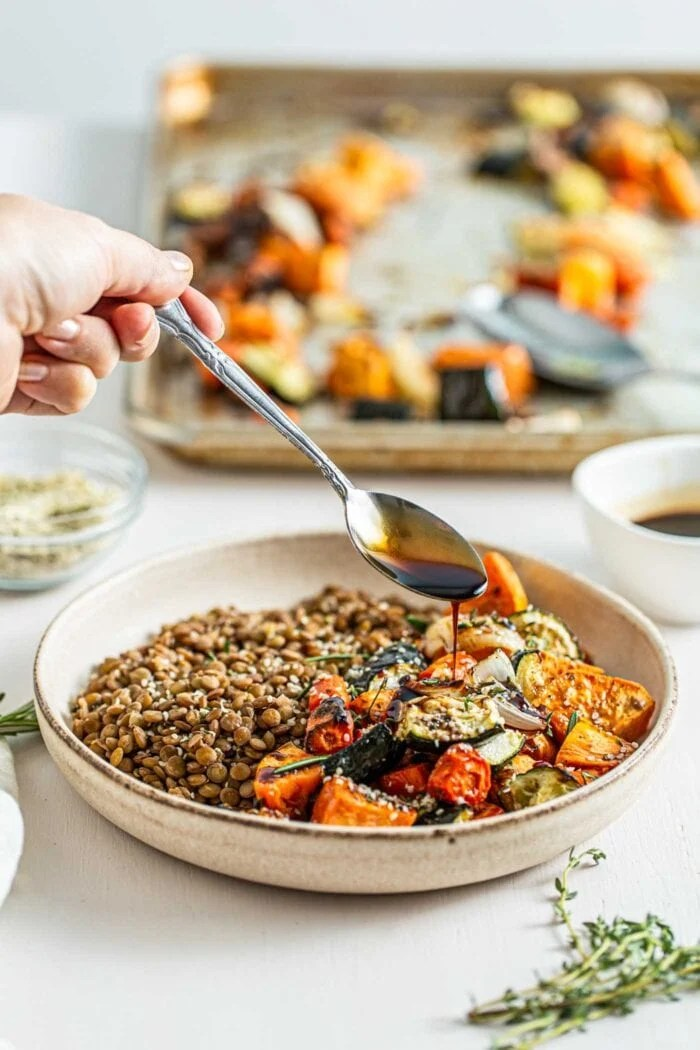 Spooning balsamic sauce over a bowl of cooked lentils and roasted vegetables.