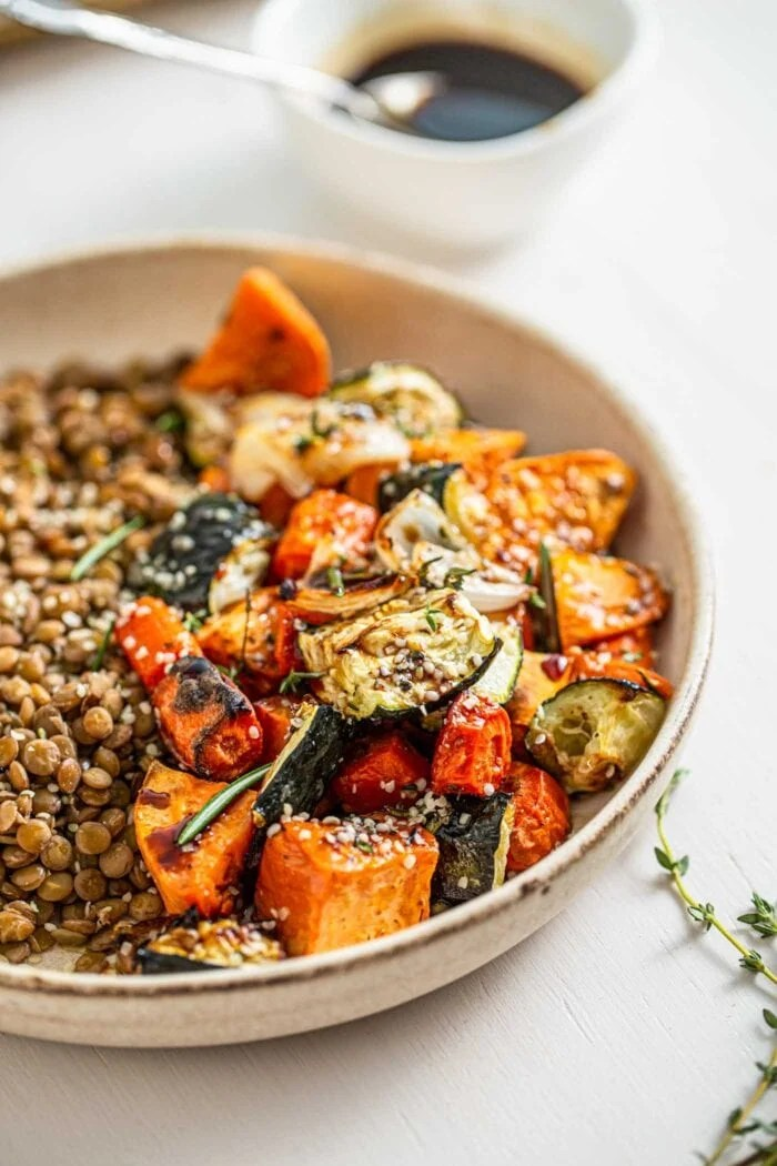 Close up of roasted zucchini, sweet potato and onions with lentils in a bowl.